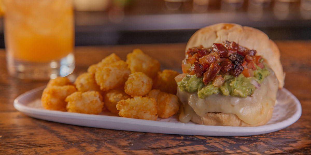 Burger with crispy bacon bits, guacamole and a side of tater tots